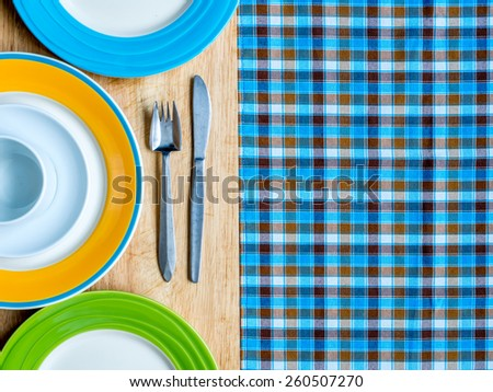 Blank plates with fork and knife on wooden table and checked tablecloth background - stock photo