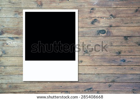 blank polaroid photo frame on brown wood plank background - stock photo