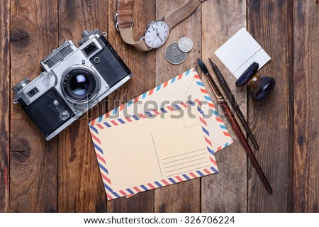 Blank post card with envelope and vintage camera, stamps, watch, ink pen and brush on wooden table still life - stock photo