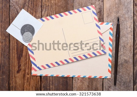 Blank post card with envelope, stamps and coins on wooden table