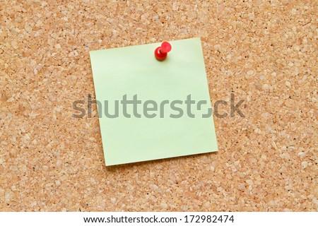blank post it note pinned to a  cork board / bulletin board  - stock photo