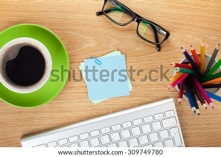 Blank post-it with office supplies and coffee cup on wooden table. Above view