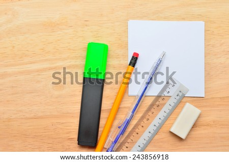 Blank post-it with pen, pencil, ruler, highlight market and eraser on office wooden table. Above view - stock photo
