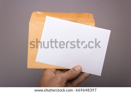 Blank postcard and envelope in hand on a gray background. Leaflet A6 mockup