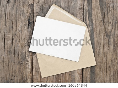 Blank postcard and envelope on old wooden background  - stock photo