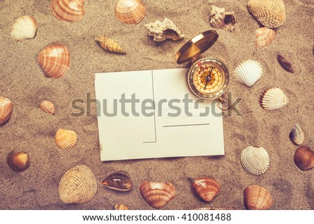 Blank postcard in hot beach sand and magnetic compass with some sea shells, copy space for summer holiday vacation message, top view, retro toned. - stock photo