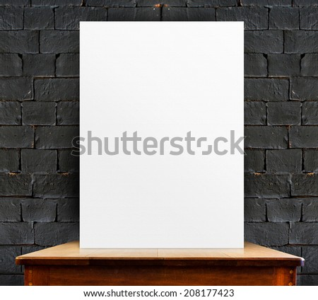 blank poster on wood table at black brick wall,perspective background