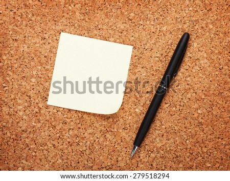 Blank postit note on cork notice board with pen  - stock photo