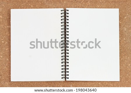 blank realistic spiral notepad notebook isolated on Cork board background - stock photo