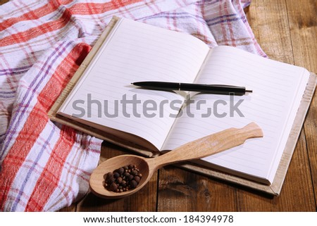 Blank recipe book on wooden table background - stock photo