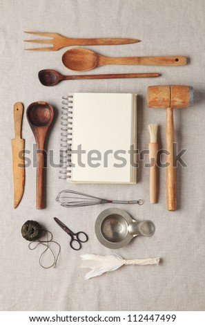 Blank recipe book or shopping list with wooden kitchen utensil on a tablecloth