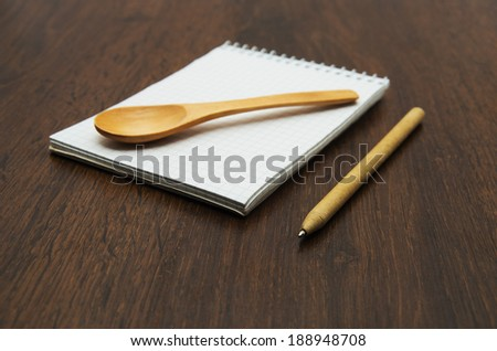 blank recipe book with wooden spoon - stock photo