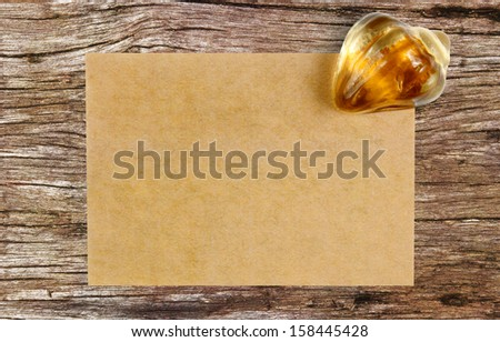 blank recycle paper with paperweight on ancient wooden table background - stock photo