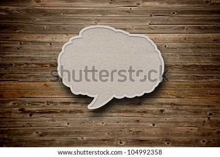 blank recycled paper speech bubble on wood background - stock photo