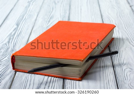 Blank red hardcover book with black pencil on  white wooden background. - stock photo