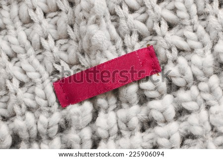 Blank red label on beige wool knitting as a background - stock photo