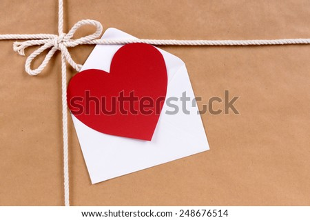 Blank red valentine card or gift tag with white envelope on a brown paper package background tied with string.  Space for copy. - stock photo