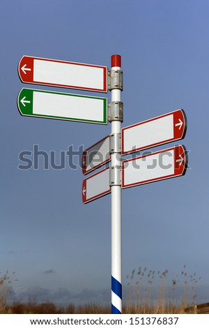 Blank road sign with six signs on pole in red and green pointing in three directions
