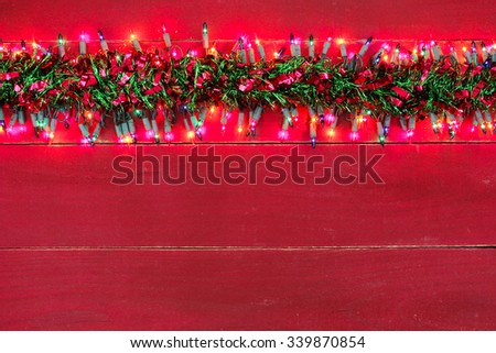 Blank rustic red wood sign with holiday lights and colorful red and green Christmas garland border - stock photo