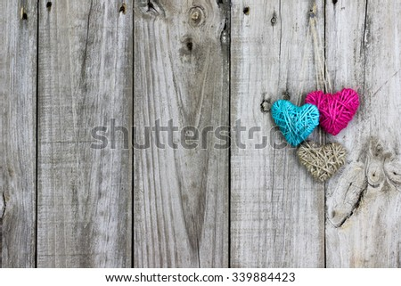 Blank Rustic Sign With Teal Blue And Pink Rope Hearts Hanging On Antique Wood Background