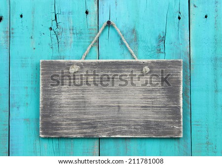 Blank rustic wood sign hanging on antique teal blue wooden background - stock photo