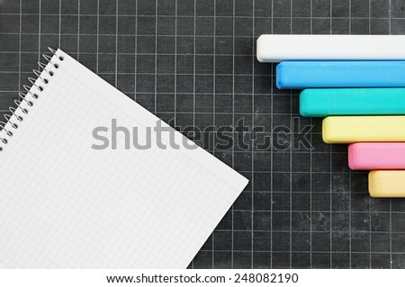 Blank school board with color chalk and blank checked note paper for text - stock photo