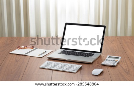 Blank screen laptop computer on wooden table - stock photo