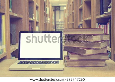 Blank screen laptop computer with old book in library room,vintage tone - stock photo