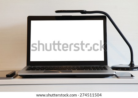 blank screen laptop computer with table lamp is on wooden desk as workplace concept - stock photo