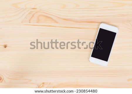 Blank screen mobile phone on wood background - stock photo
