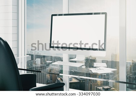 Blank screen of computer monitor on glassy table, mock up - stock photo