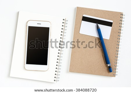 Blank screen of mobile on notebook paper with pvc card and pen on office desk - stock photo