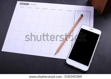 blank screen smartphone and planner schedule on black wooden background