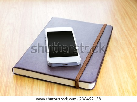 Blank screen Smartphone on Brown Hard cover notebook with elastic strap on wooden table in perspective view,Template for adding your content - stock photo