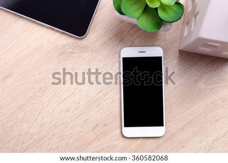 Blank screen smartphone, tablet and office supplies on wooden background - stock photo