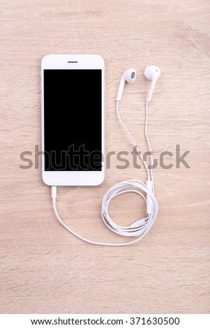 Blank screen smartphone with earphone on wooden background