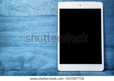 Blank screen Tablet computer on blue wooden table  - stock photo