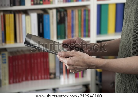 blank screen tablet in woman hands at library - stock photo