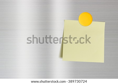 Blank sheet of note paper attached on a refrigerator stainless steel door with yellow fridge magnet. For leaving several messages i.e. info, news, memo, suggestion, recommendation, hint, alert, notice - stock photo