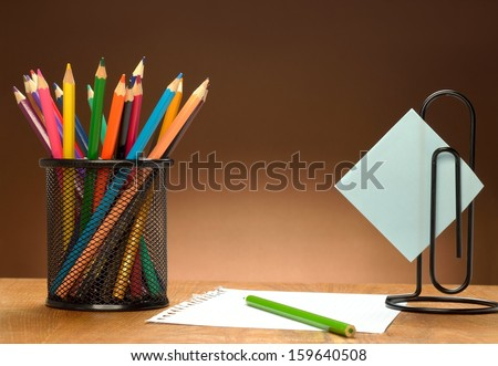 Blank sheet of paper and colored pencils on a wooden table - stock photo