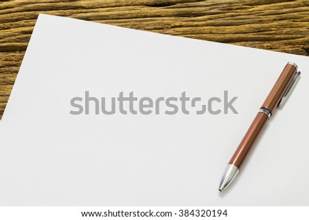 Blank sheet of paper and pen on old wooden background. - stock photo