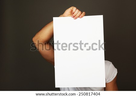 Blank sheet of paper in male hand on dark background - stock photo