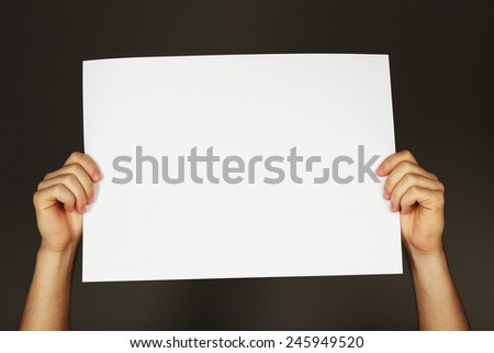 Blank sheet of paper in male hands on dark background - stock photo