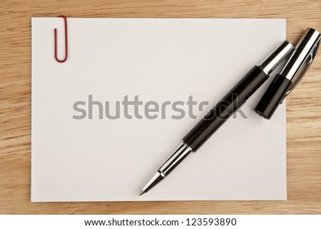 Blank sheet of paper with pen on wooden background - stock photo