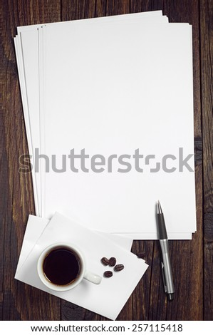 Blank sheet of white paper and a cup of coffee on dark wooden table, top view - stock photo