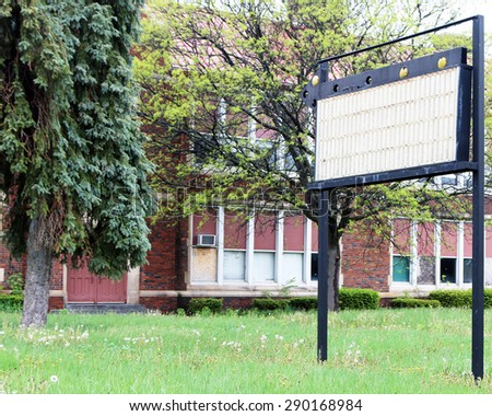 Blank sign in front of an abandoned building. - stock photo
