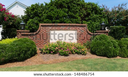 Blank sign on a brick wall at the entrance of a subdivision - stock photo