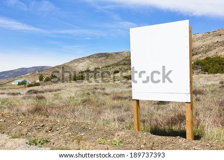 Blank sign posted in a rural scene.