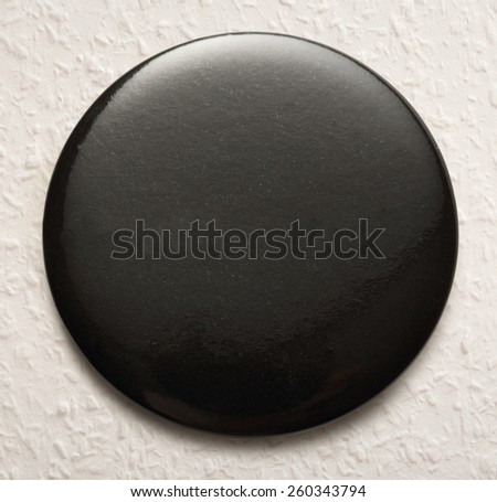 Blank single black round badge in closeup - stock photo