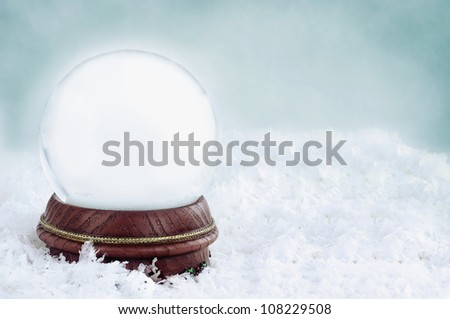 Blank snow globe with with copy space available against a blue background. - stock photo